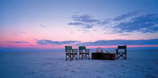 3 chair on beach scene in open plain with dust background in botswana