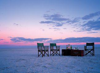 3 chair on beach scene in open plain with dust background in botswana