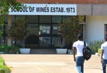 a picture of 3 maile zambia students walking up to the entrance of the school of mines which was established in 1973