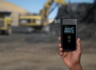 Man holding a breathalyzer tester in an open pit mining environment
