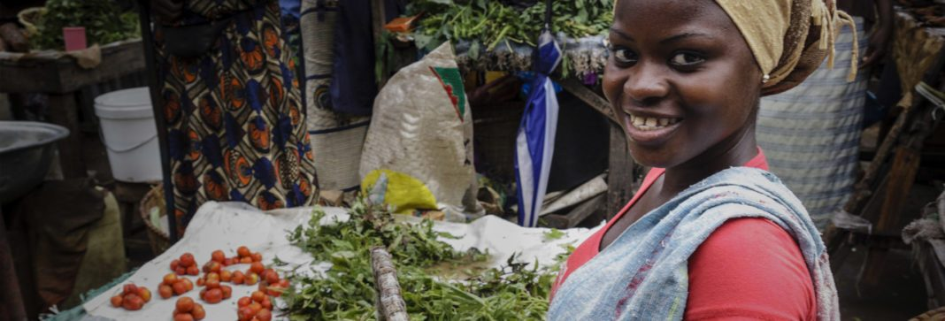 Black woman smiling in an informal market setting