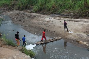 hildren crossing the stream over a makeshift stone path
